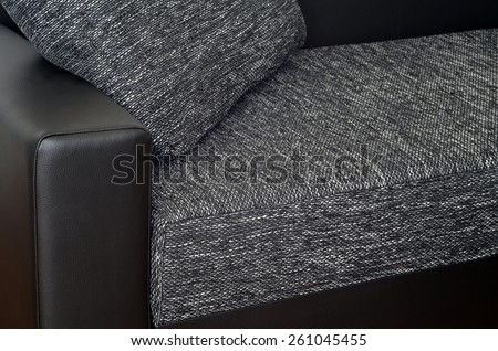 Detail of black leather armchair on black and white cloth sofa - stock photo
