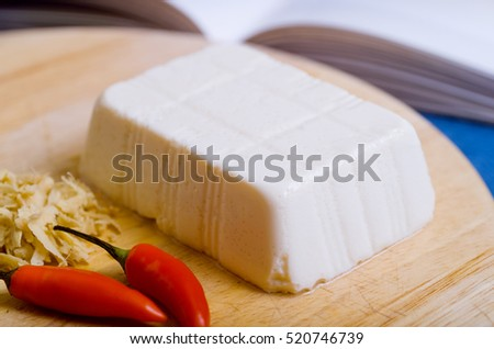 Detail of block of soft Tofu on a kitchen chopping board