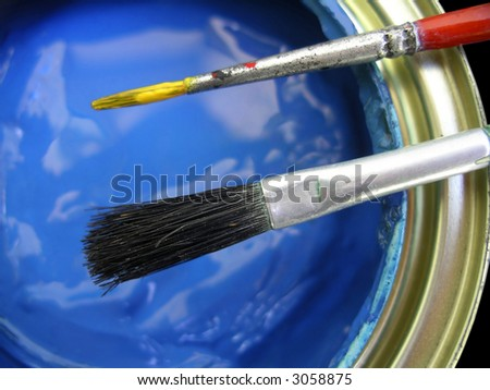 Detail of blue paint can with two brushes on top - stock photo