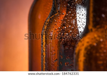 detail of bottle of fresh beer with drops on wood background - stock photo