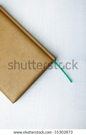 Detail of brown leather book laying on wooden table - stock photo