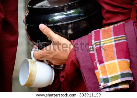 Detail of buddhist monk in red robe, his hands holding a bowl and cup - stock photo
