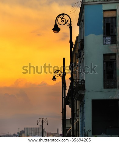 Detail of building facade and street lamps against dramatic sunset sky - stock photo