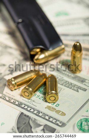 detail of bullet on US dollar banknotes, crime or corruption concept
