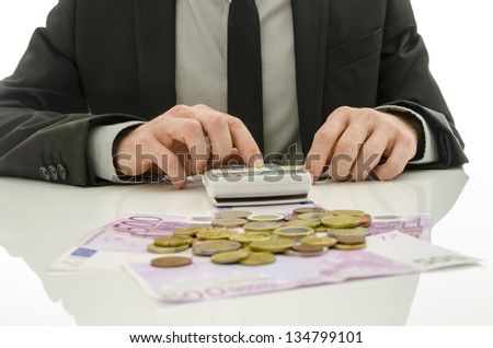 Detail of businessman working on calculator counting expenses. With Euro coins and banknotes on his white table. - stock photo