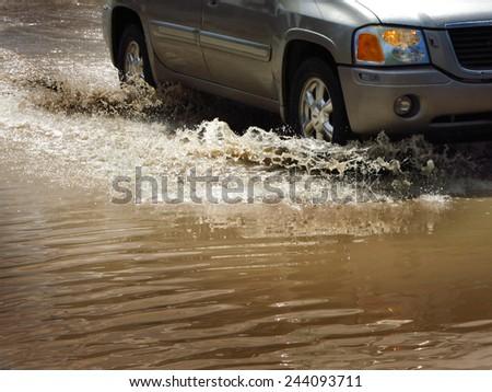 Detail of car driving through flood waters splashing - stock photo
