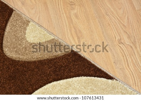 Detail of carpet in brown, beige and white colors on laminate - stock photo