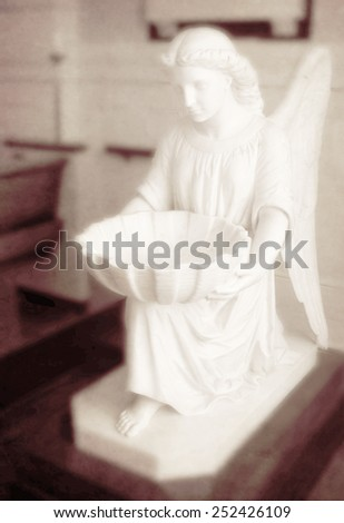 Detail of carved angel baptism basin in christian church - stock photo