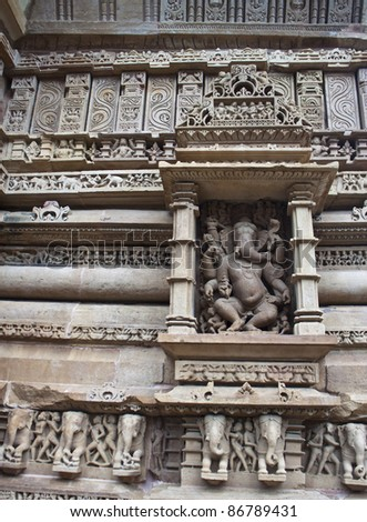 Detail of carving on a temple in Khajuraho, Madhya Pradesh, India. God Ganesh in the centre.