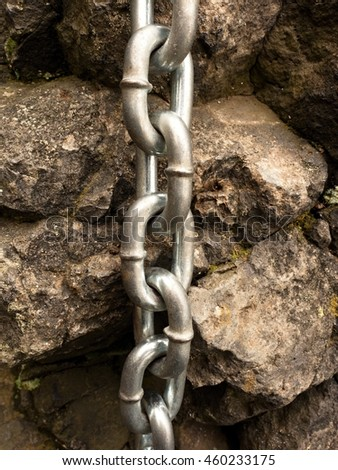 Detail of chain and steel bolt anchor eye in sandstone rock. The end knot of steel chain. Climbers path via ferrata. Iron chain fixed in block.