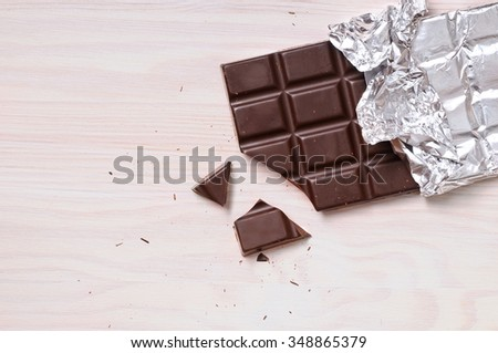 Detail of chocolate bar with silver wrapping on a wooden table with a broken portion. Horizontal composition. Top view - stock photo