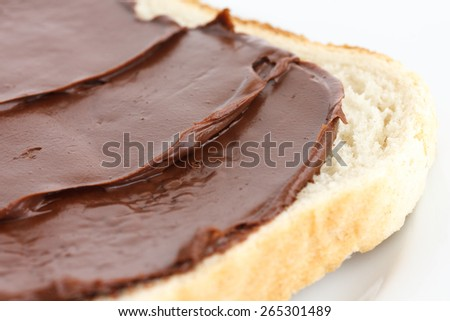 Detail of chocolate nut spread on white sandwich bread. - stock photo