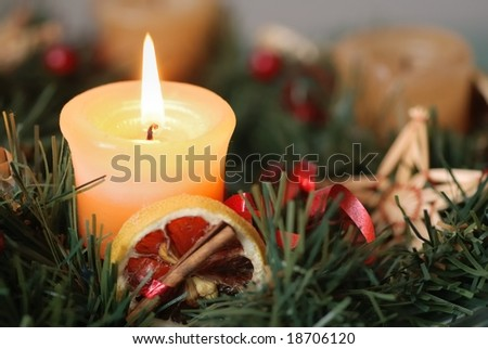 Detail of christmas advent wreath with burning candle. Focus on candle. - stock photo
