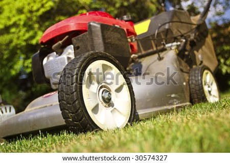 detail of classic Lawn Mower on green grass background - stock photo