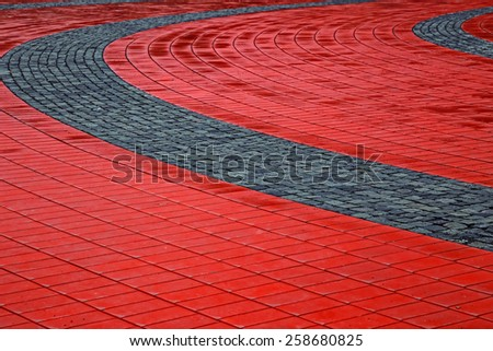 Detail of cobblestone sidewalk made of cubic red and gray stones. Pedestrian public square after rain. - stock photo