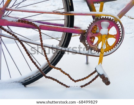detail of colorful bicycle with broken chain in snow