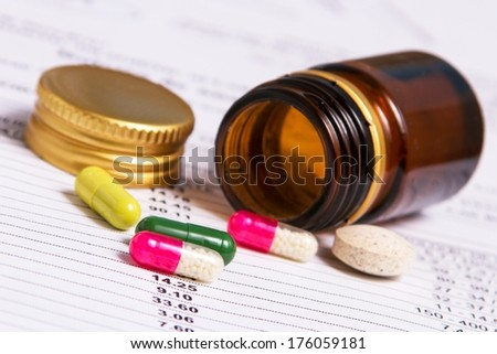 Detail of colorful pills out of container - stock photo