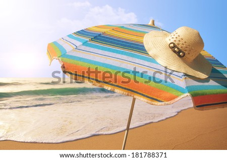 Detail of colorful sunshade and straw hat in the beach on a sunny summer day  - stock photo
