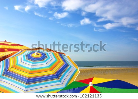 Detail of colorful sunshades in the beach on a sunny summer day - stock photo