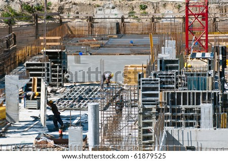 Detail of construction site with workers, scaffolding, crane and assets - stock photo