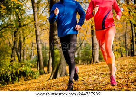 Detail of couple jogging together in beautiful autumn nature - stock photo