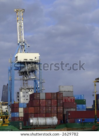 Detail of crane over stacked containers in freighting port in the Med
