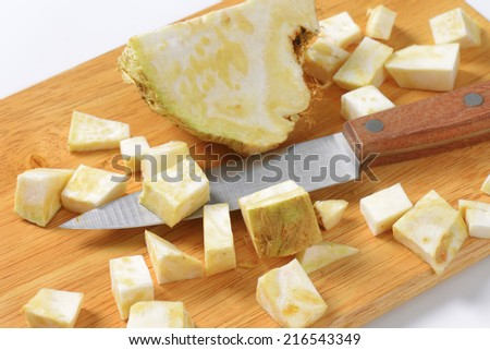 detail of cubed celery and kitchen knife on wooden cutting board - stock photo