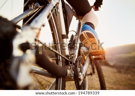 Detail of cyclist man feet riding mountain bike on outdoor trail in sunny meadow - stock photo