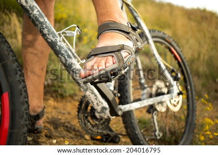 Detail of cyclist man feet riding mountain bike on outdoor trail in sunny meadow. focus on leg - stock photo