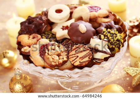 Detail of delicious Christmas cookies with candles in golden tone - stock photo