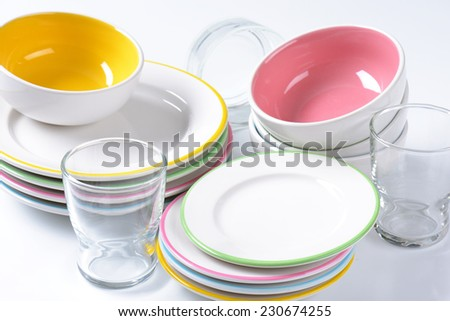 detail of dinnerware set - stacked dessert plates, soup bowls and glass