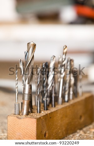Detail of drills on workshop table, shallow focus - stock photo