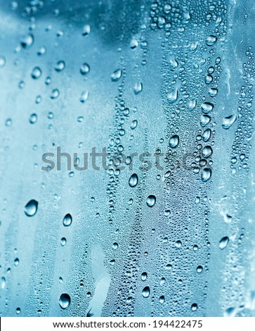 Detail of drops of water flowing down a window. - stock photo
