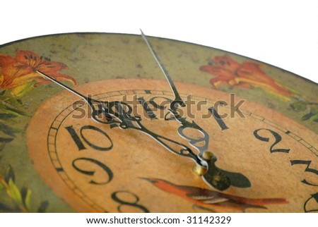 Detail of dusty old clock reading almost 12 o'clock shallow depth of field on white background. The clock is decorated in a tole painting style design in fall colors of gold and orange with green - stock photo