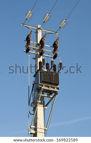 Detail of Electric Pylon with Transformer against blue sky - stock photo