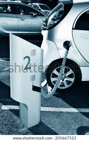 Detail of electrical car in charging position connected to an electric power source - stock photo