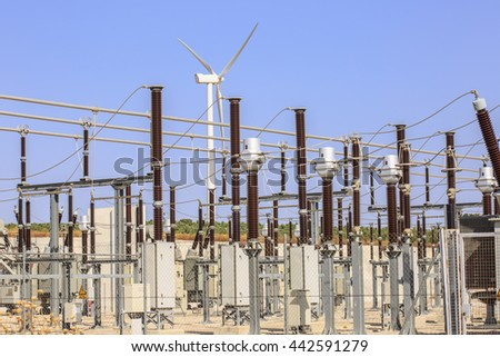 Detail of electrical substation of a wind farm, with a wind turbine at background