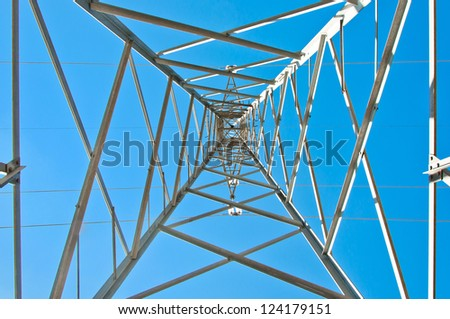 Detail of electricity pylon against blue sky: high voltage electric pillar from below - stock photo