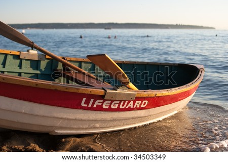 Detail of empty lifeguard rowboat on beach at sunset - stock photo