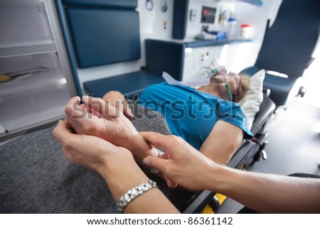 Detail of EMT worker measuring pulse on senior woman patient in ambulance - stock photo