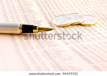 detail of euro coins and a golden pen  on the financial newspaper - stock photo