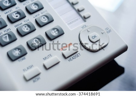 Detail of executive VoIP desk phone buttons. Shallow depth of field - focus on the center of the phone