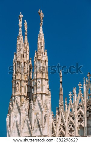 Detail of facade Milan Cathedral or Duomo di Milano is the cathedral church of Milan, Italy. Blue sunny sky background. - stock photo