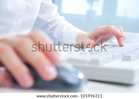 Detail of female hands using a computer on office background - stock photo