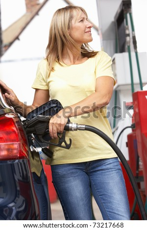 Detail Of Female Motorist Filling Car With Diesel At Petrol Station - stock photo