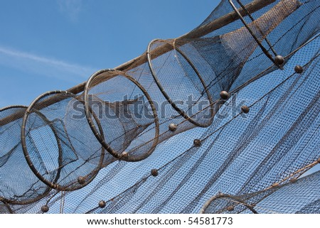 Detail of fishnet drying in the sun against the blue sky - stock photo