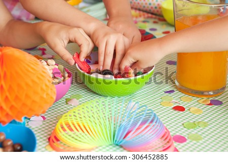 Detail of four children hands taking sweets and party food at a home garden birthday party having fun, outdoors. Kids celebrating, eating and enjoying a colorful party on sunny day, lifestyle. - stock photo