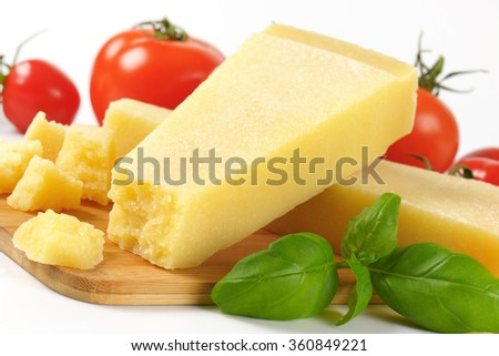 detail of fresh parmesan cheese and vegetable garnish on wooden cutting board - stock photo