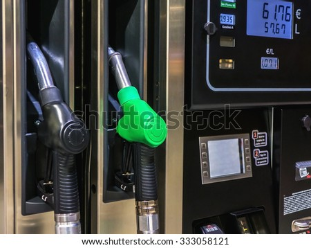 Detail of gasoline pump nozzles in a gas station with prices in euros - stock photo