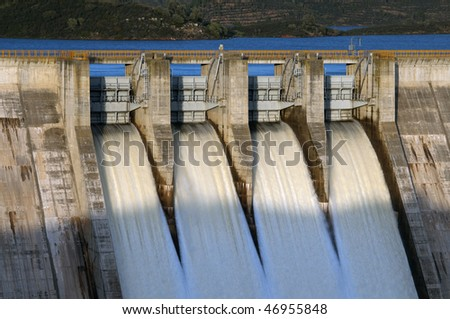 detail of gates open from hydroelectric power station - stock photo
